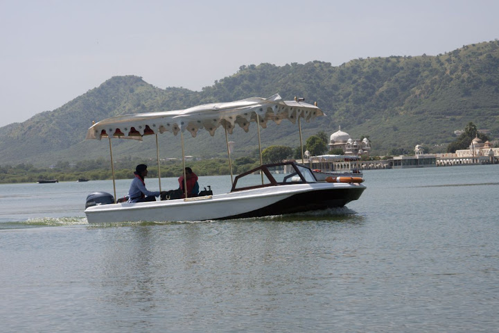 Boat carrying a single tourist on the Pichola Lake in Udaipur - view of the Jag Mandir Palace in the background